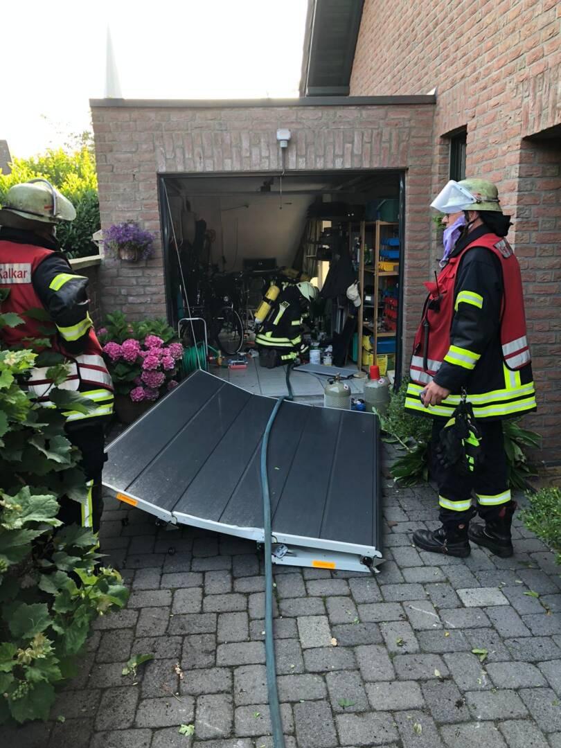Feuerwehrmänner vor Garage